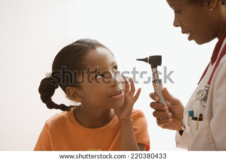 Female doctor looking inside patient's ear - stock photo