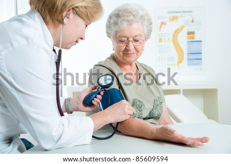 Female doctor measuring blood pressure of senior woman - stock photo