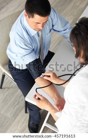 Female doctor measuring man blood pressure with tonometer - stock photo