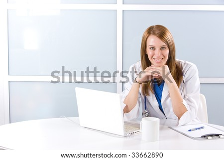 Female doctor on computer at desk in a modern office - stock photo