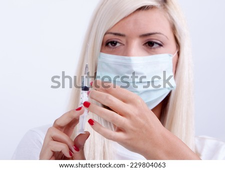 Female doctor or nurse in medical mask holding syringe with injection  - stock photo