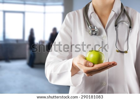 Female doctor's hand holding green apple. Close up shot on blue blurred background. Concept of Healthcare And Medicine. Copy space - stock photo