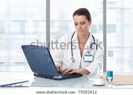 Female doctor sitting at table with laptop, looking down, working.? - stock photo