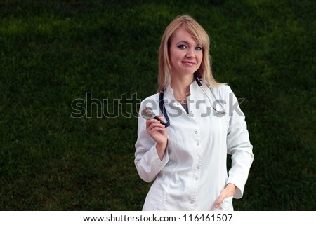 Female doctor smiling on the background of the grass. - stock photo