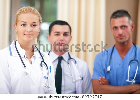 Female Doctor standing in Front of her team in the hospital - stock photo