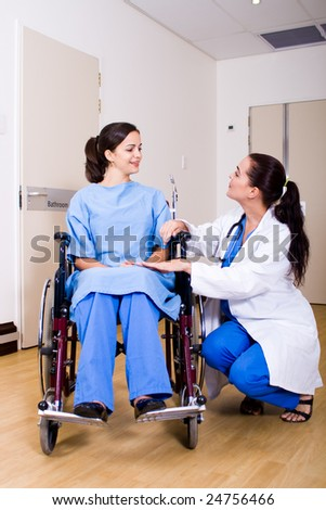 female doctor talking to her patient on wheelchair - stock photo