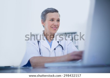 Female doctor using her laptop computer in medical office - stock photo