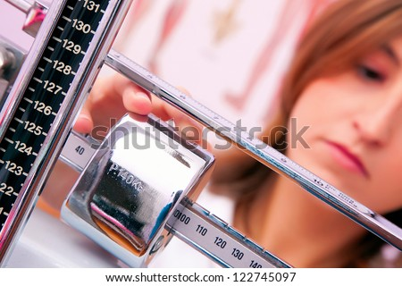 female doctor weighing - stock photo