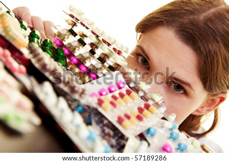 Female doctor with heap of many colorful pills - stock photo