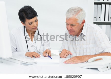 Female doctor with male patient reading reports at medical office - stock photo