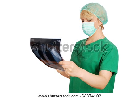 female doctor with mask examining x-ray - stock photo