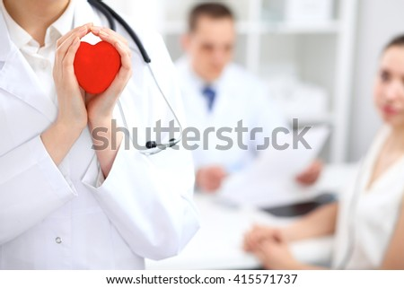 Female doctor with stethoscope holding heart.  Doctor and patient sitting in the background - stock photo