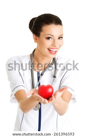 Female doctor with stethoscope holding heart model. - stock photo