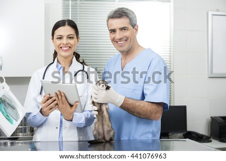 Female Doctor With Tablet Computer By Coworker Holding Weasel - stock photo