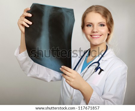Female doctor with X-ray picture isolated on grey background - stock photo