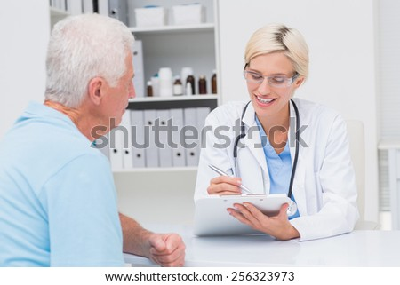 Female doctor writing prescription for senior man in clinic - stock photo