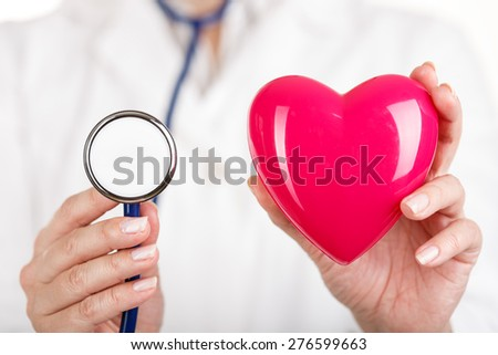 Female doctors's hands holding red toy heart and stethoscope's head near. Doctor's hands closeup. Medical help or insurance concept. Cardiology care and health. - stock photo