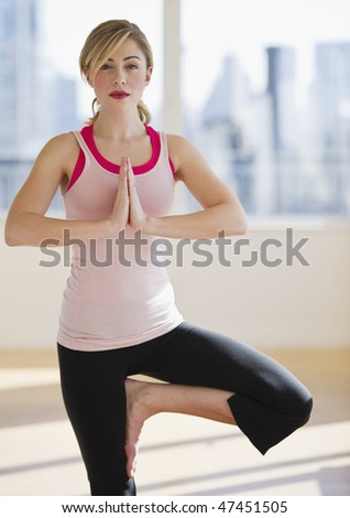 female doing balanced yoga position alone in gym - stock photo