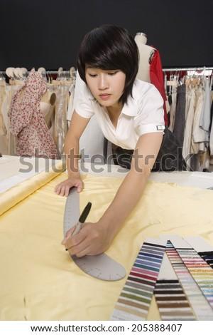 Female dressmaker measuring fabric - stock photo