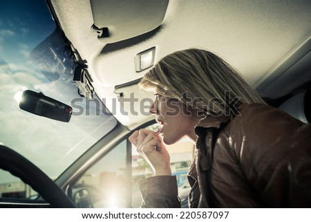Female driver doing makeup in her car - stock photo