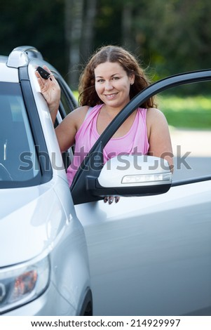 Female driver near opened car door with key in hand - stock photo