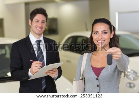 Female driver showing a key after bying a new car at new car showroom - stock photo