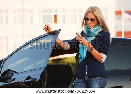 Female driver with a mobile phone - stock photo