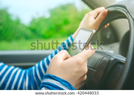 Female driving car and texting sms message on smartphone, using mobile phone in traffic, selective focus - stock photo