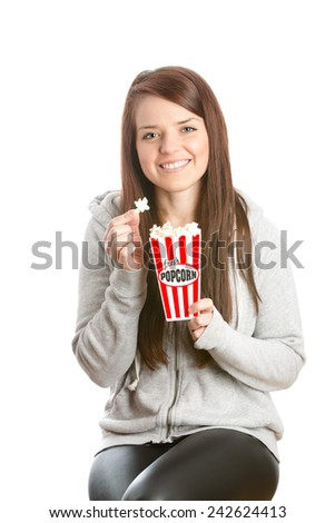 Female Eating Popcorn - This is a shot of a beautiful young woman enjoying some popcorn. Shot on an isolated white background. - stock photo