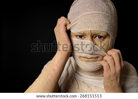 female egyptian mummy pulling at bandages halloween concept - stock photo