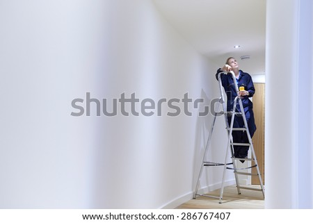 Female Electrician Installing Lights In Ceiling - stock photo