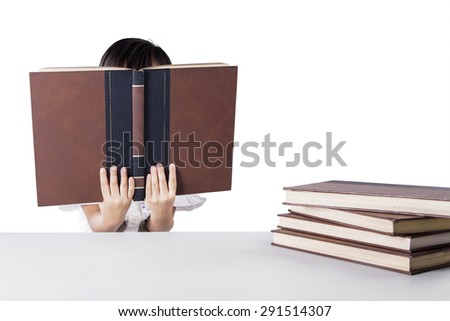 Female elementary school student reading literature while covering her face, isolated on white - stock photo