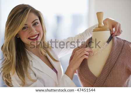 female employee dressing mannequin in clothing store and looking at camera - stock photo