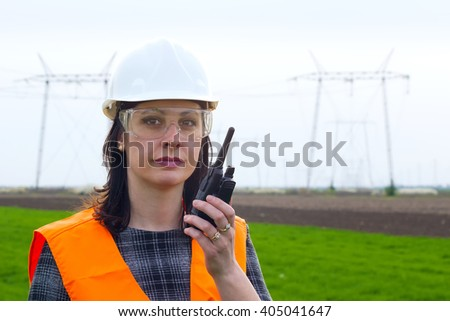 Female engineer for high voltage ; Supervising female engineer for electrification using walkie- talkies near the transmission line - stock photo