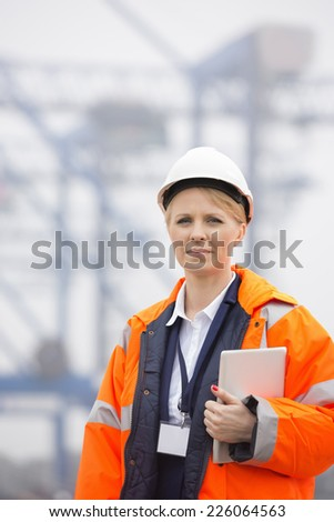 Female engineer holding tablet PC in shipping yard - stock photo