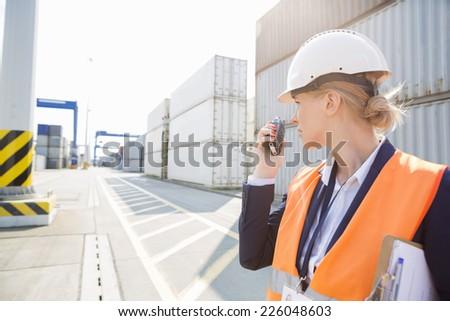 Female engineer using walkie-talkie in shipping yard - stock photo