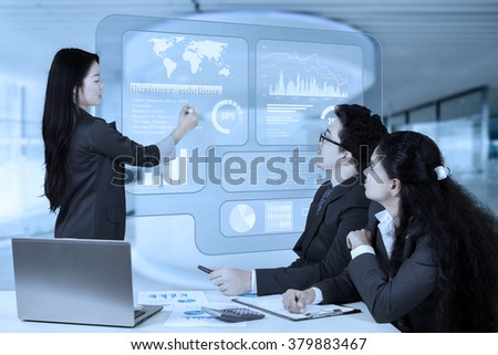 Female entrepreneur using a virtual screen to delivering a presentation and explaining business solutions - stock photo