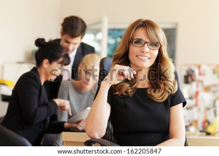 Female executive smiling in the office, with her colleagues in background. Shallow focus. - stock photo