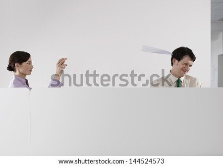 Female executive throwing a paper aeroplane at male colleague in the office - stock photo