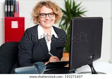 Female executive writing notes on clipboard looking at you - stock photo