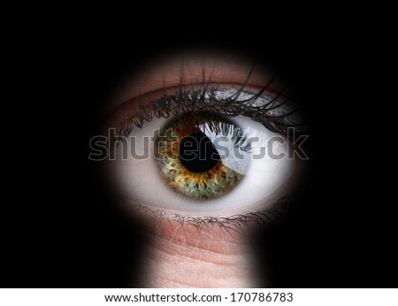 Female eye peeking through a keyhole concept for curiosity, stalker, surveillance and security - stock photo