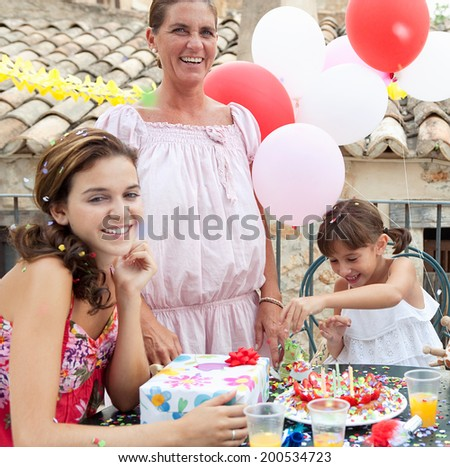 Female family group celebrating a young girl birthday during a summer day, around a table with a birthday cake and gifts and a happy birthday girl playing with a present. Family enjoying outdoors. - stock photo
