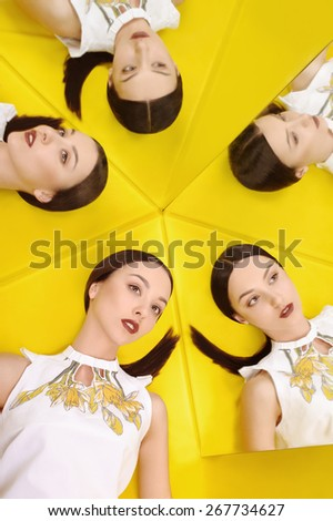 Female fashion concept. Beautiful girl posing with a mirrors on a yellow background. - stock photo