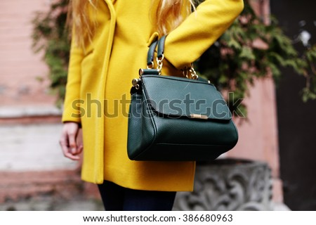 Female fashion concept. Close up. Colorful detail of yellow coat and green leather bag.  Street style - stock photo