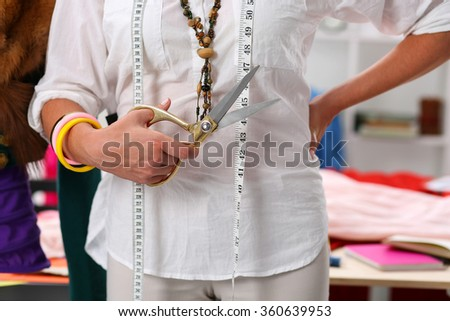 Female fashion designer holding big golden tailor scissors in hand closeup. Creating garment, dress sewing service, seamstress ready do take measurement and make new suit concept - stock photo