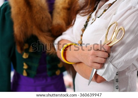 Female fashion designer holding big golden tailor scissors in hand with old style gown in background. Creating garment, dress sewing service, seamstress ready to take measurement and sew suit concept - stock photo