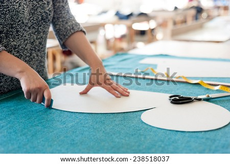 Female fashion designer working with sketches at studio and choosing cloth - stock photo