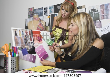 Female fashion designers working at desk - stock photo