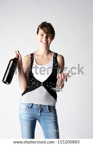 female fashion model posing at light background and holding black wine bottle and wineglass - stock photo