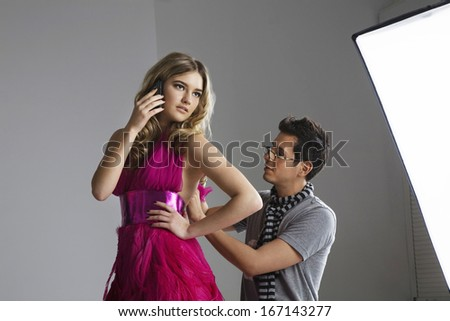 Female fashion model using cell phone while designer adjusting her dress in studio - stock photo